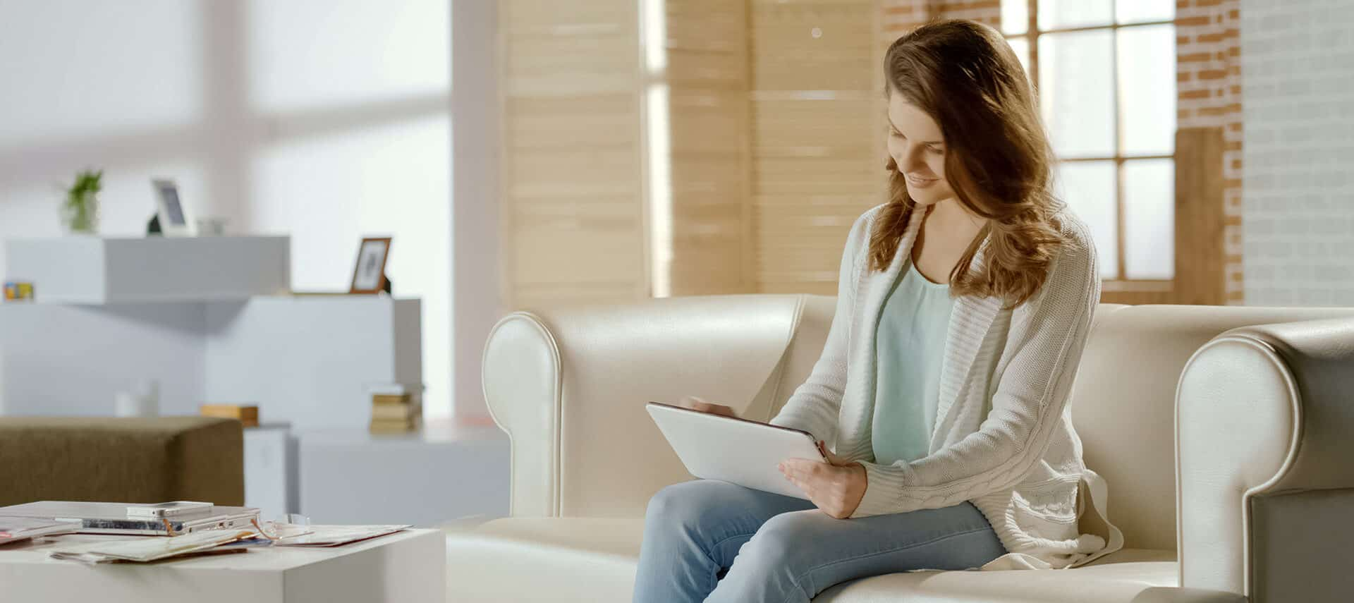 Brunette woman on sofa with a tablet in a living room.