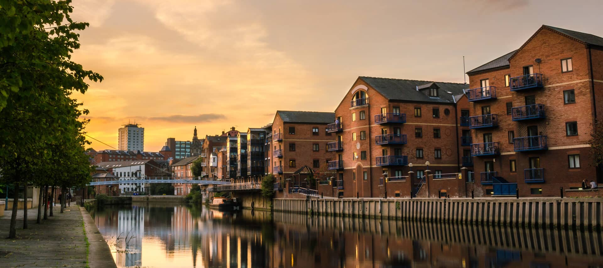 Line of brick buildings along the banks of a river at sunset.