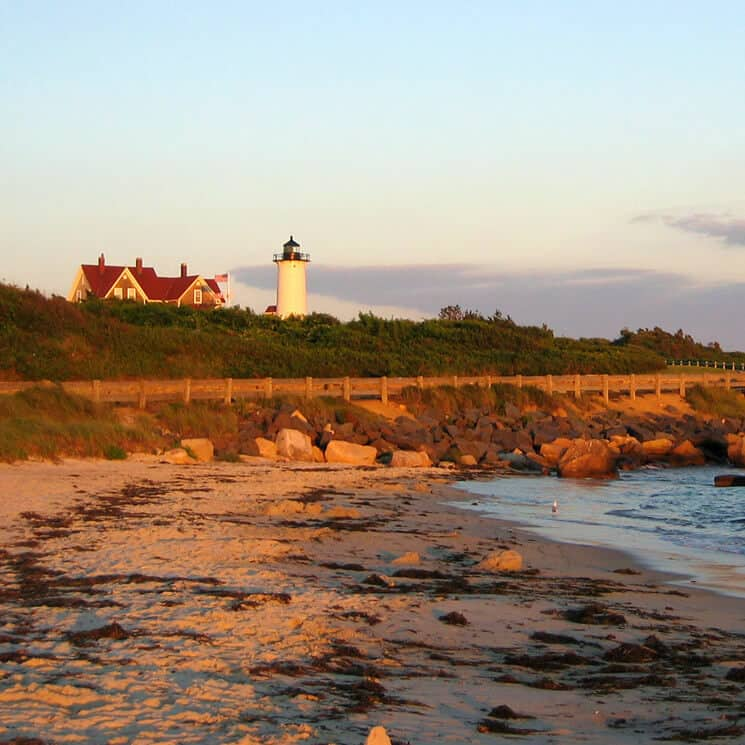 Lighthouse on bluff overlooking the Atlantic ocean at sunset
