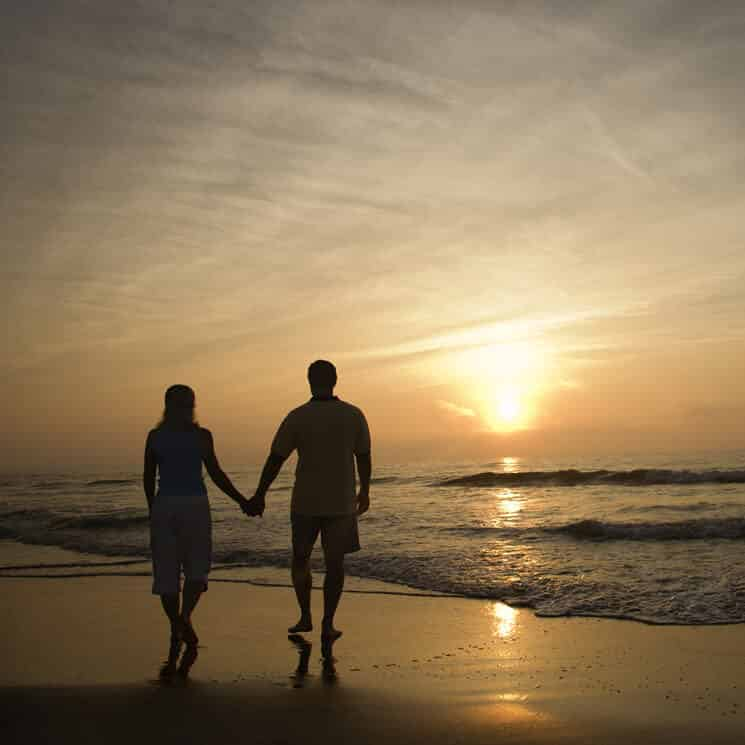 Couple walking along beach in the sunset